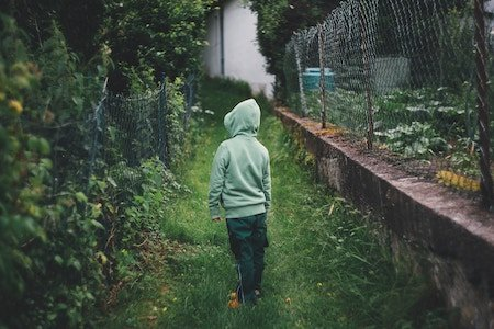 Back of child wearing hoodie looking at lush garden