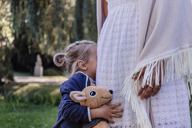 little girl hiding in woman's white skirt holding a stuffed animal