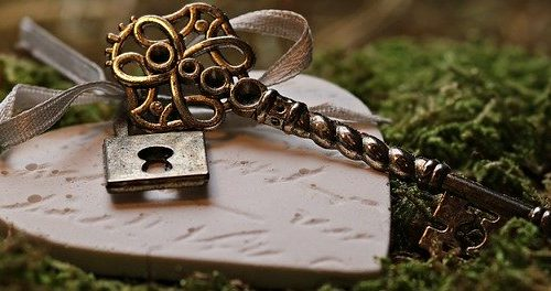 Closeup of old decorative skeleton key tied to a heart wiht ribbon and all lying on green moss